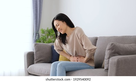attractive japanese woman with stomach ache sitting sofa in the living room