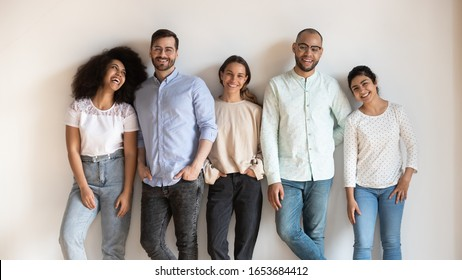 Attractive jovial multi-ethnic friends girls guys leaned on grey beige wall pose smiling looking at camera feels happy. Concept of racial equality and friendship, millennial generation people portrait