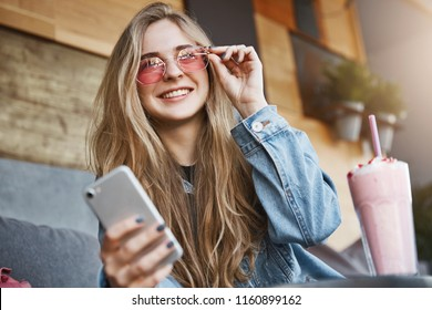 Attractive and joyful caucasian blond woman in trendy sunglasses, touching rim of eyewear and smiling broadly while gazing at city streets, holding smartphone, chatting during lunch, drinking cocktail