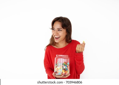 Attractive joyful young Latin female wearing red sweater smiling broadly, enjoying sweets out of glass jar. Pretty girl eating candies or jelly beans after dinner, having relaxed and cheerful look