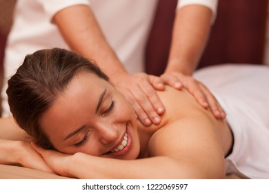 Attractive joyful young woman smiling cheerfully why professional masseur massaging her shoulder. Gorgeous woman relaxing at day spa. Therapist giving soothing massage to female client. Beauty concept