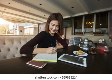 Attractive Kazakh  female accountant making statistic report working with database and financial documentation concentrated on fulfilling task working in coworking pace with wifi zone using technology