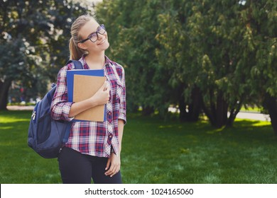 Attractive kind smiling student girl with books in park outdoors, looking away, dreaming or thinking during break, having rest in campus. Education concept, copy space