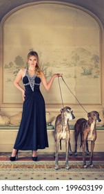 attractive lady in black dress with two greyhounds