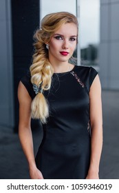 Attractive lady with blong hair in long evening dress stands next to the building with mirror windows