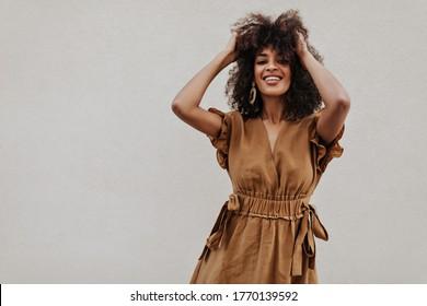 Attraktive Dame in braunem Kleid knöpft die Haare draußen. Charmante, dunkelhäutige, lockige Frau in stilvollem Sommeroutfit lächelt auf grauem Hintergrund.