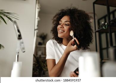 Attraktive Dame Contouring Gesicht. Dunkelhäutige Frau hält Make-up-Bürste, Pulver, schaut in den Spiegel zu Hause.
