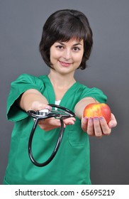 Attractive lady doctor with stethoscope and fresh apple on gray background