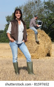 Attractive lady farmer standing in front of her husband on a haystack using a laptop with the screen left blank