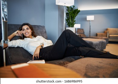 Attractive lady lying on comfortable daybed and having phone conversation stock photo