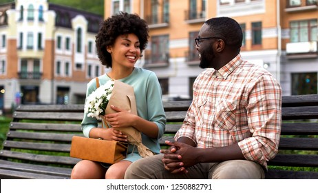Attractive lady meeting boyfriend on first date, man presenting white flowers