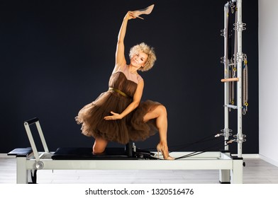 Attractive lady practicing yoga in evening dress