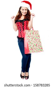 Attractive lady in santa cap, holding shopping bag