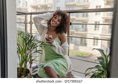 Attraktive Dame in Seidenkleid hält Kaffeemaschine auf dem Balkon. Auf der Terrasse befindet sich eine charmante, dunkelhäutige Frau mit weißem Zickler.