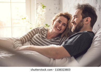 Attractive lady is smiling to partner while they are hanging out in dormitory during morning time. Relaxed carefree man is looking ahead and gently taking woman hand