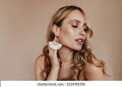 Attractive lady wears elegant earrings posing in studio. Amazing caucasian girl with long shiny hair looking away.