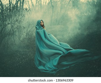 attractive large lady in long blue summer light waving raincoat runs through forest with bare trees and mysterious white smoke and magical fog, charming sorceress escapes from a fairytale monster