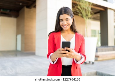 Attractive Latin business manager text messaging on mobile phone outside office
