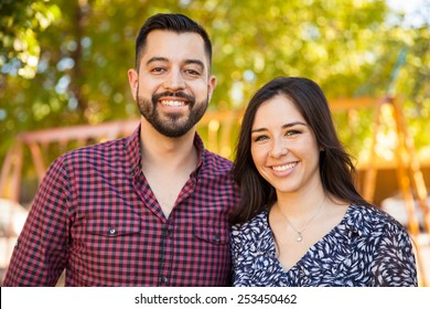 Attractive Latin young couple enjoying a sunny day outdoors and smiling