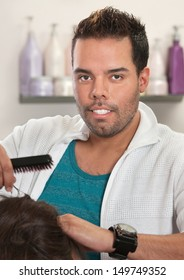 Attractive Latino male hair stylist working with hairbrush