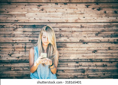 Attractive laughing female standing with mobile phone against wooden wall background with copy space area, pretty casually-dressed hipster woman looking away smiling and feeling so happy in joy