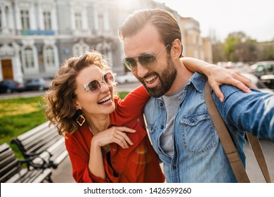 attractive laughing man and woman traveling together, stylish couple in love taking selfie photos on phone on romantic trip, sunny summer city, wearing shirt, sunglasses, travelers having fun