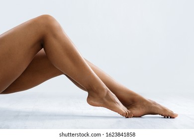 Attractive legs of black woman over grey background, free space, hair removal procedures