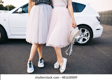 Attractive legs of fashion models in tulle skirts amd sneakers on white car background