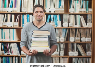 Attractive librarian holding a pile of books standing in library smiling at camera