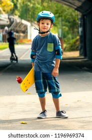 Attractive little boy with yellow skateboard in his hand