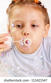 Attractive little girl blowing soap bubbles