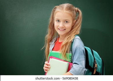 Attractive little girl with books standing on green blackboard background