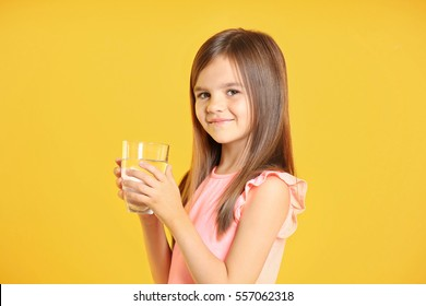 Attractive little girl holding glass of water on yellow background