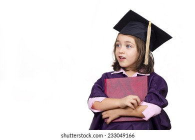 Attractive little girl in large graduation cap and gown with diploma over white background
