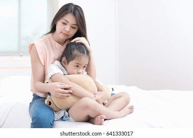 Attractive little girl is looking angry away crossed her arms hands gesture back to her mother and eyes looking unhappy while she mistakes sitting on the bed at home.