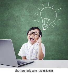 Attractive little girl looks happy get idea, pointing at a picture of light bulb with laptop on desk