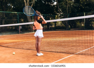 Attractive little girl in sportwear is playing tennis