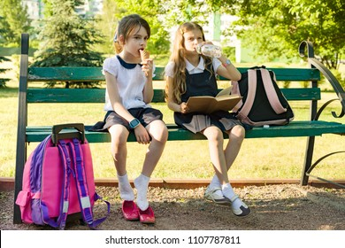 Attractive little girlfriends schoolgirls with backpacks, Girls rest on bench in the park after school, eat ice cream, drink water, read book, talk