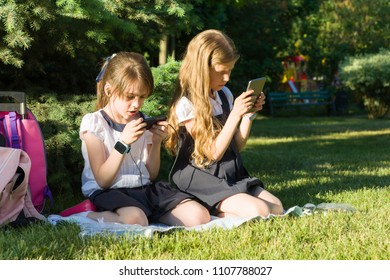 Attractive little girlfriends schoolgirls with backpacks, smartphones on a meadow in the park. People, children, technology, friends and friendship concept