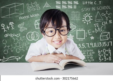 Attractive little student smiling on the camera with a book on the table, shot in the class with scribble background on the chalkboard