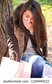 Attractive long haired brunette with colored shopping bags sitting under the tree in public park