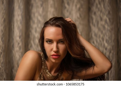 Attractive long haired brunette posing with hand on head looking at camera