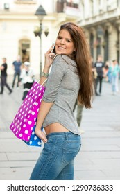 Attractive long haired young woman with colored paper bags walking down the street after shopping and talking over the phone