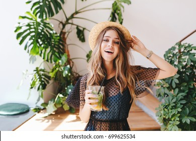 Attractive long-haired girl in hat with nude makeup standing with cocktail in room with big plants in pots. Indoor portrait of glad young woman in wristwatch holding glass of juice.