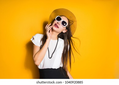 attractive long-haired girl model in black hat and sunglasses posing on yellow background