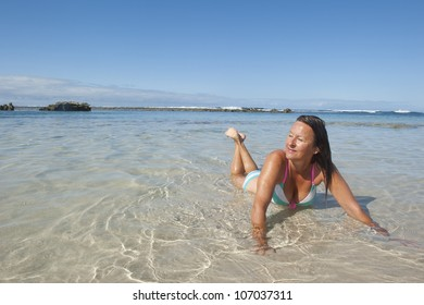 An attractive looking middle aged bikini woman lying seductive in the shallow water at a tropical beach, with ocean and blue sky as background and copy space.