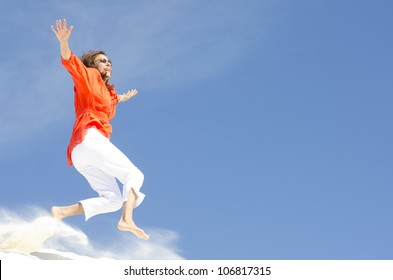An attractive looking middle aged woman is jumping cheerful and with a happy expression down a sand dune, isolated with clear blue sky as background and copy space.