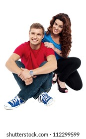 Attractive love couple sitting relaxed on floor. Indoor studio shot
