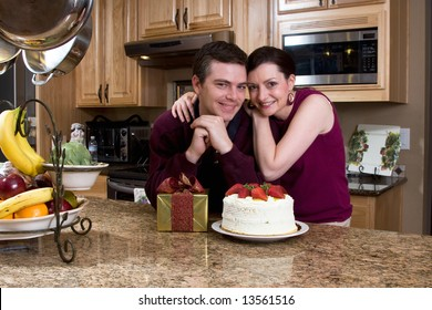 Attractive loving couple hugging and leaning on their kitchen counter which holds a cake and a gift. They are smiling at the camera.