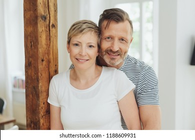 Attractive loving middle-aged couple in a close embrace standing indoors at home smiling at the camera